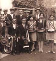 """Après le défilé, quelques musiciens, dont Belo et son basson, entourés des """"prieuresses"""" et de quelques amis (vers 1925). Document : archives du musée de Pigna."""